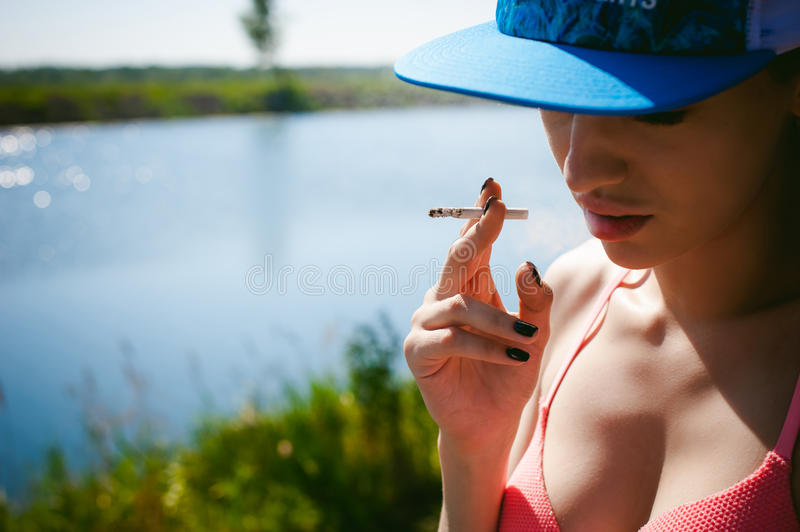 Young woman in swimsuit in snapback on her head. Smokes cigarette, resting, enjoying summer on shore of pond royalty free stock photos