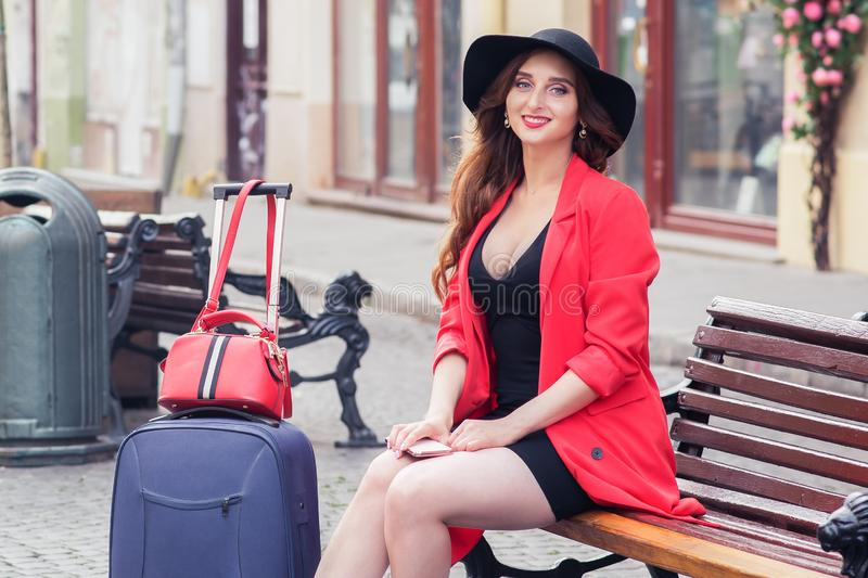 Young sexy woman traveler with suitcases is sitting on a bench outdoors stock photos