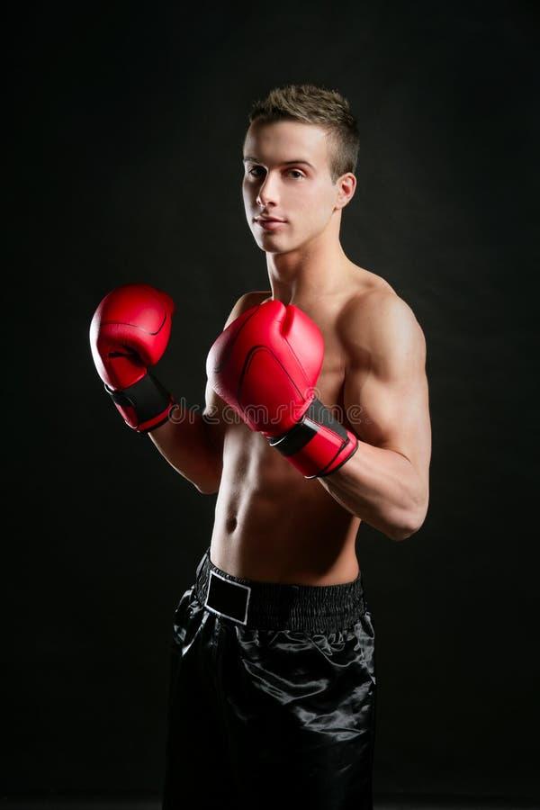 Young shaped man boxing, studio shot