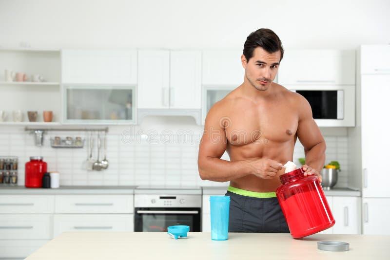 Young shirtless athletic man preparing protein shake in kitchen royalty free stock photos