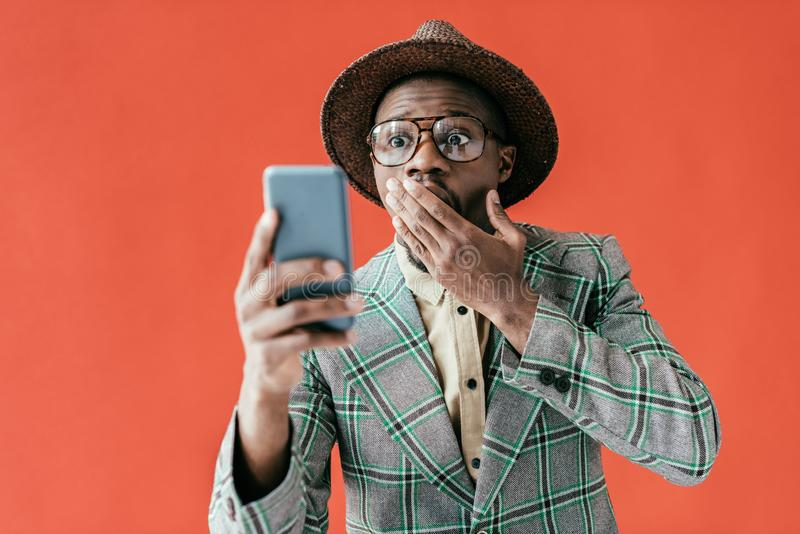 Young shocked african american man looking at smartphone. Isolated on red stock photo