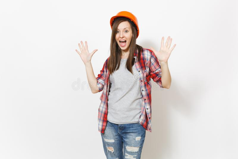 Young shocked beautiful woman in protective construction orange helmet spreading hands with copy space isolated on white stock photo