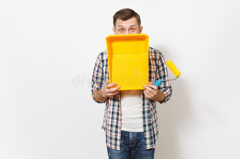 Young shocked handsome man holding paint roller for wall painting and covering face with paint tray isolated on white royalty free stock photo