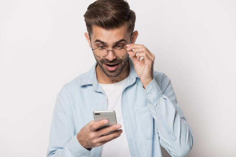Young shocked man reading email with unbelievable news. royalty free stock photos