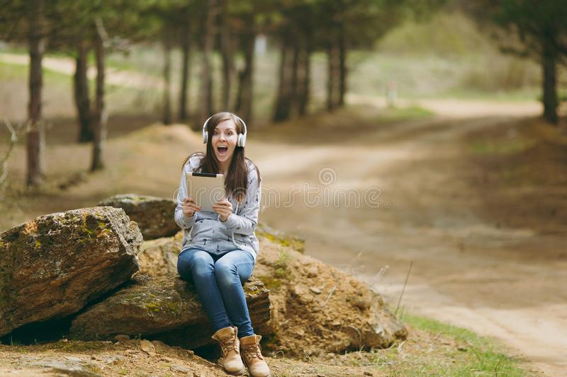 Young shocked overjoyed woman in casual clothes with headphones sitting on stone using tablet pc computer in city park. Or forest on green blurred background stock images