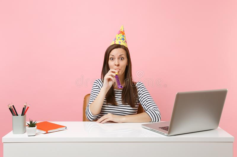 Young shocked woman in birthday party hat with playing pipe celebrating while sit work at white desk with pc laptop. Isolated on pastel pink background royalty free stock photography
