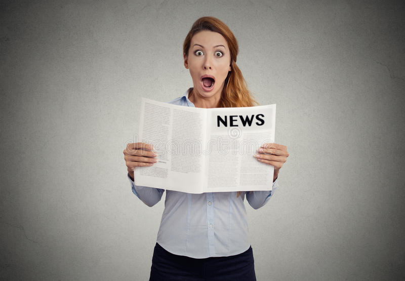 Young shocked woman reading magazine stock photography