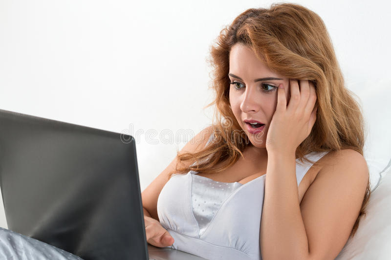Young shocked woman reading something at laptop stock photo