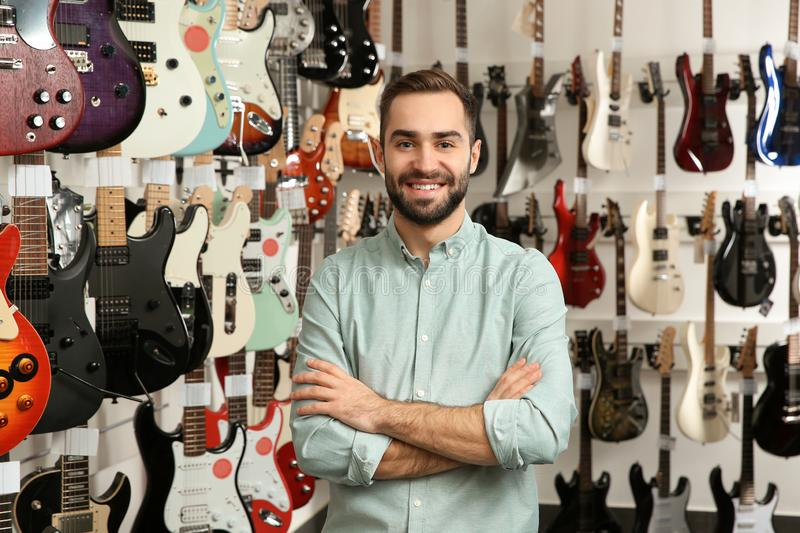 Young shop assistant near guitars. In music store royalty free stock images