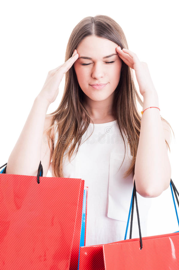 Young shopaholic having a headache and looking tired. After a long day of shopping on white royalty free stock photography