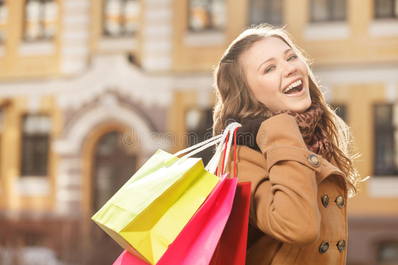 Young shopaholic woman. Beautiful young women holding the shopping bags in her hands and smiling at camera stock images