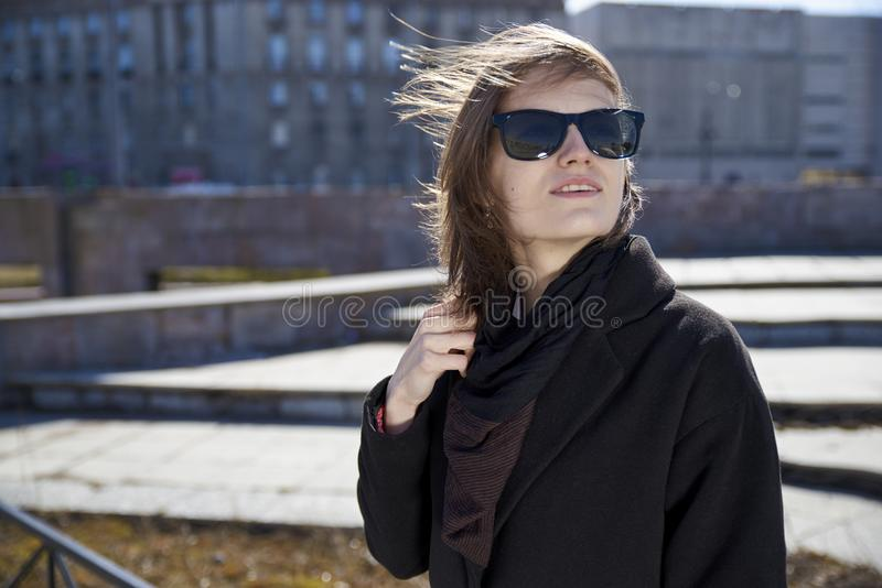 Young short haired girl in sunglasses and stylish black coat posing for portrait on grey urban city background stock image