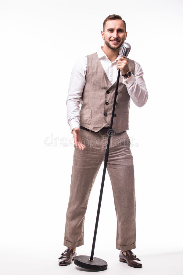 Young showman in suit singing with emotions gesture over the microphone with energy. royalty free stock photos