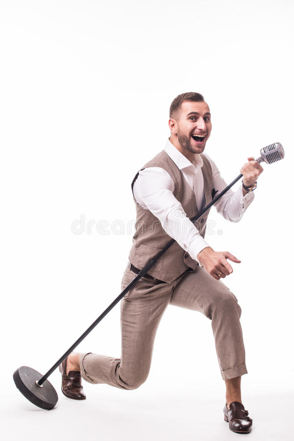 Young showman in suit singing with emotions and pointed gesture over the microphone with energy royalty free stock images