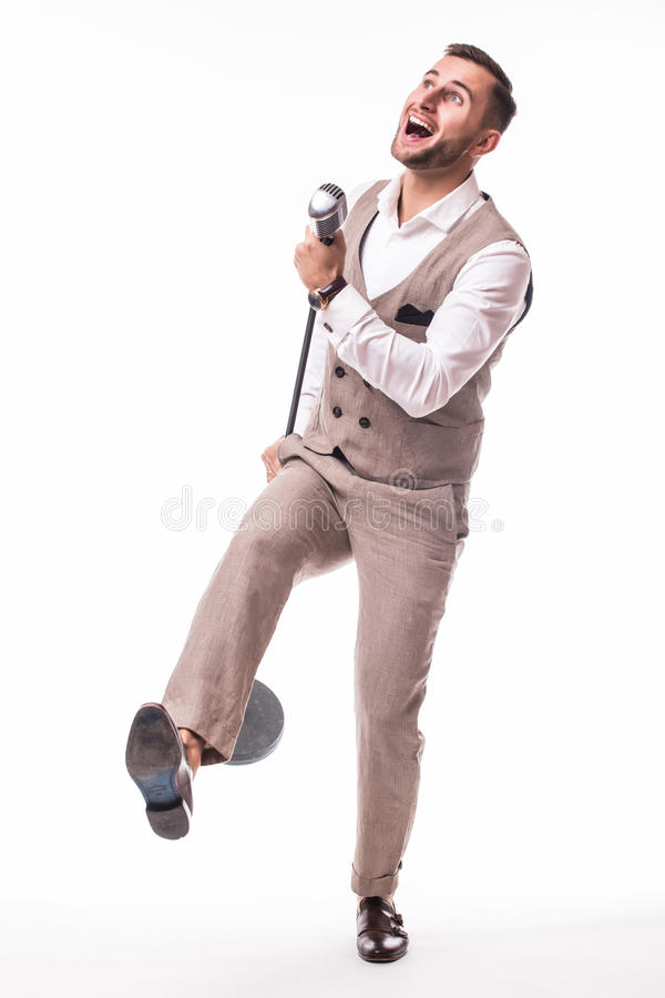 Young showman in suit singing with emotions and pointed gesture over the microphone with energy stock photo