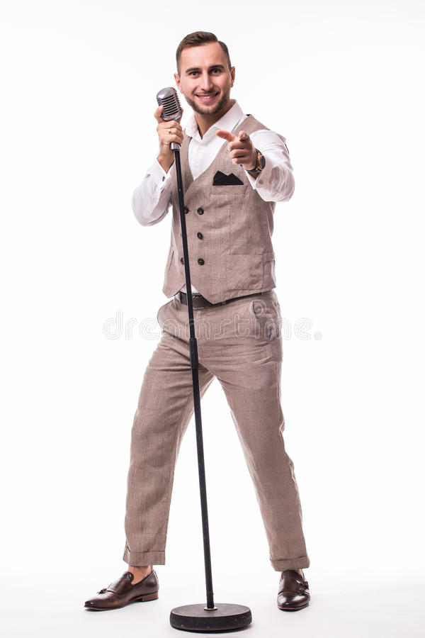 Young showman in suit singing with emotions and pointed gesture over the microphone with energy stock image
