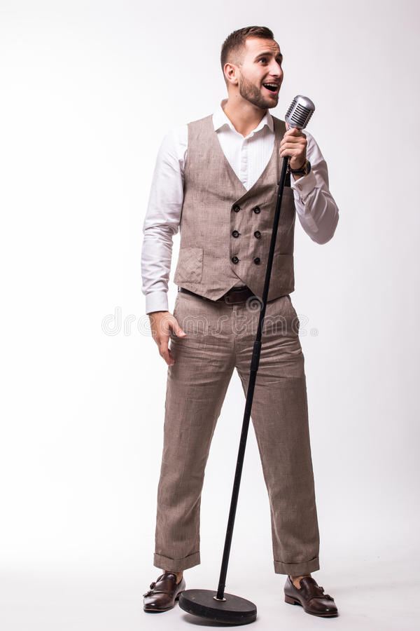 Young showman in suit singing with emotions and pointed gesture over the microphone with energy stock photography