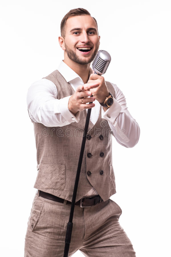 Young showman in suit singing with emotions and pointed gesture over the microphone with energy royalty free stock photos