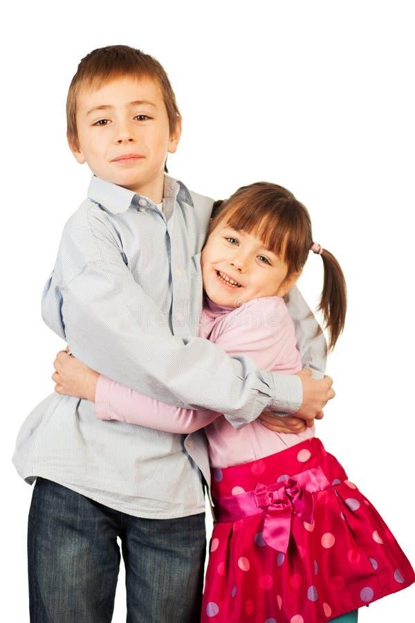 Young siblings hugging stock photo