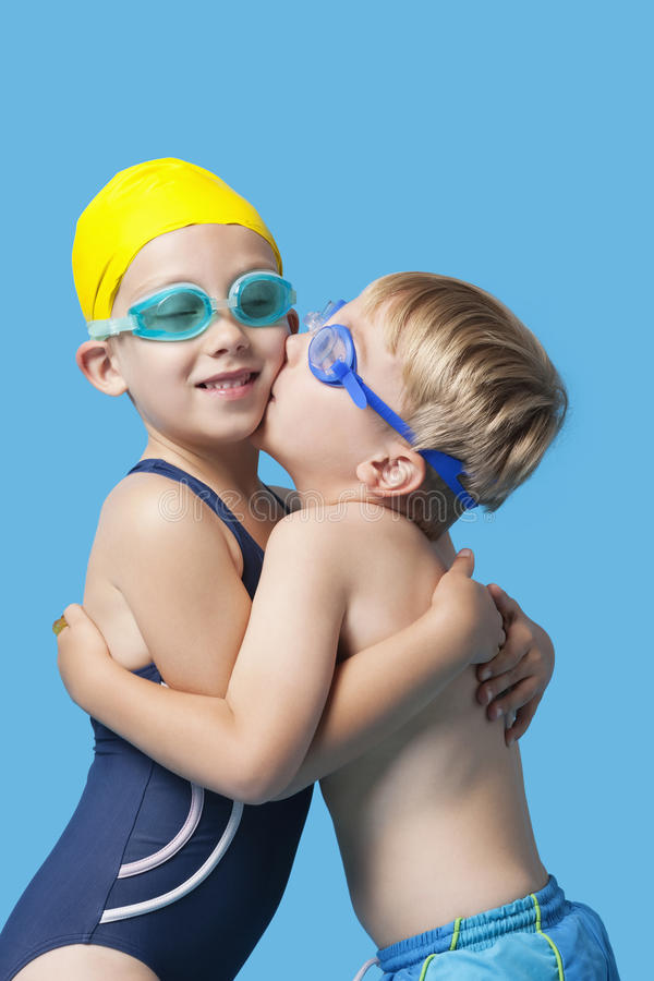 Download Young Siblings In Swimwear Embracing And Kissing Over Blue Background Stock Photo - Image: 30855298