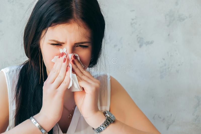 Young sick girl sitting alone at work office sneeze holding tissue handkerchief and blowing wiping her running nose. Student girl. Has seasonal allergy or royalty free stock photos