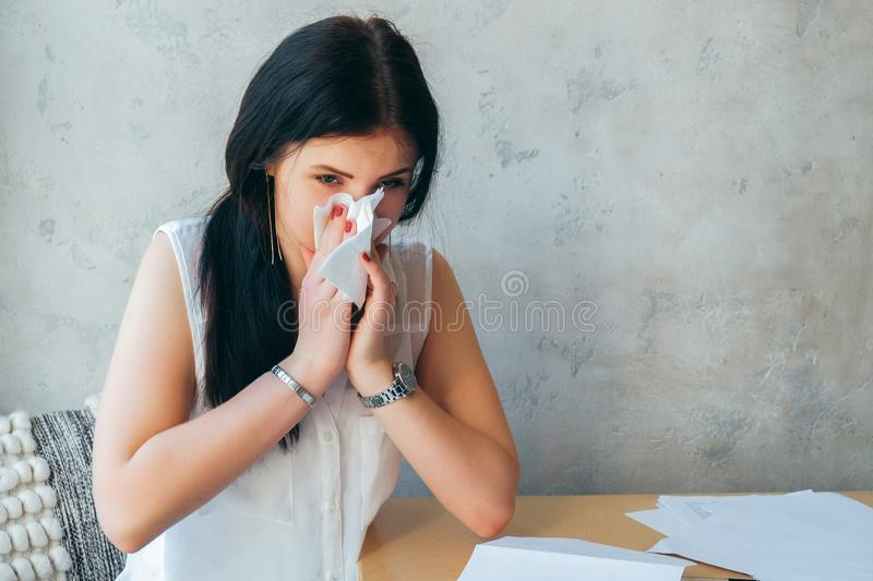 Young sick girl sitting alone at work office sneeze holding tissue handkerchief and blowing wiping her running nose. Student girl stock photo