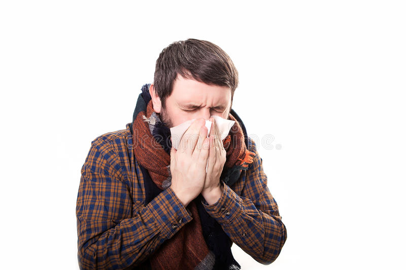 Young sick and ill man in bed holding tissue cleaning snotty nose having temperature feeling bad infected by winter stock photo