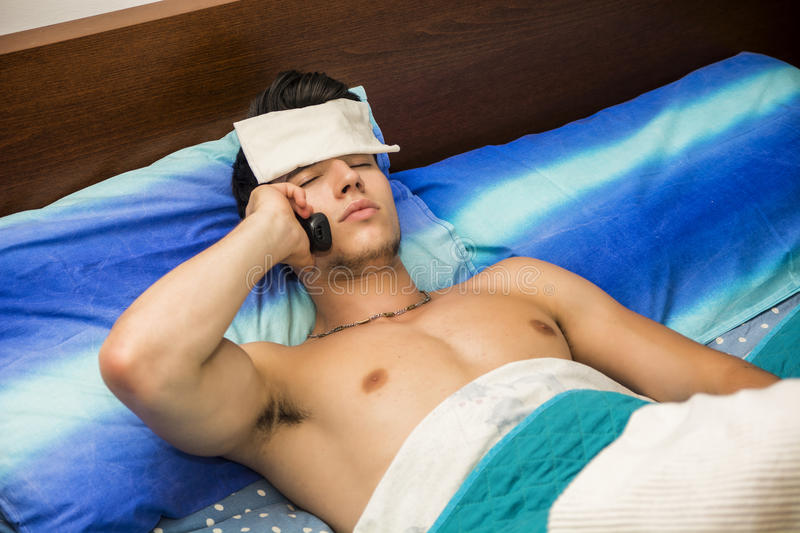 Young sick or unwell man in bed calling doctor royalty free stock photos