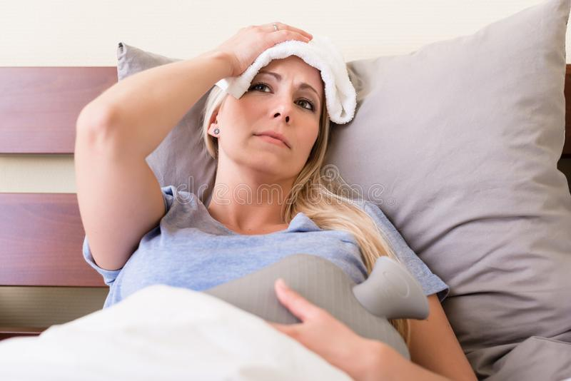 Young sick woman with fever lying in bed royalty free stock images
