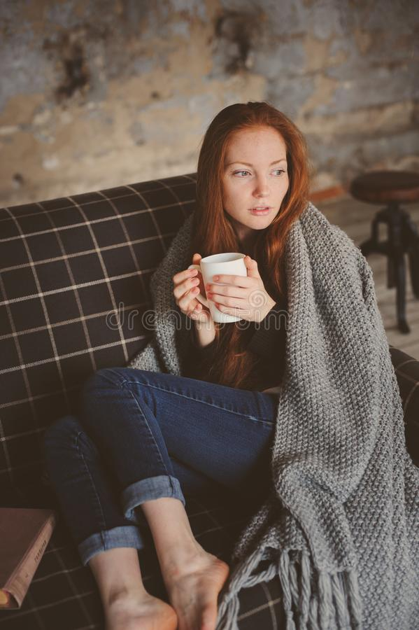 Young sick woman healing with hot drink at home on cozy couch. Wrapped in knitted blanket royalty free stock photos