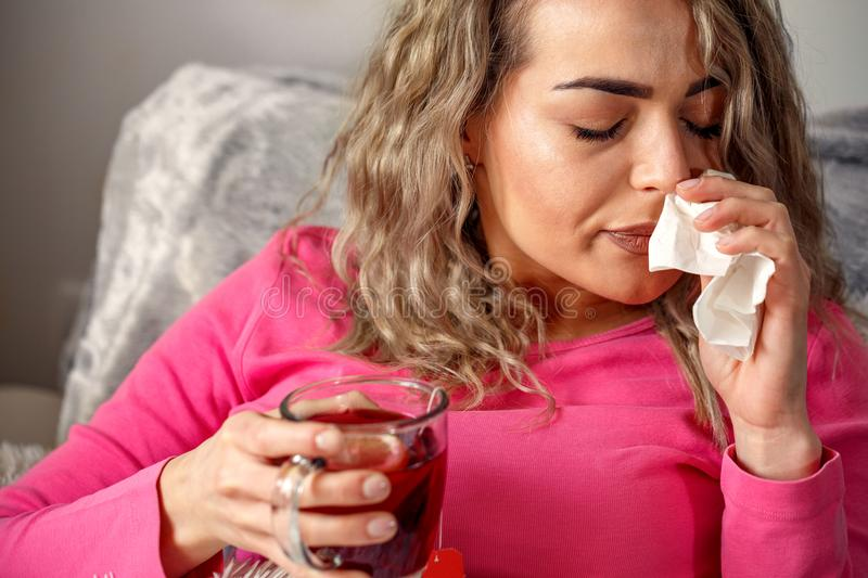 Sick woman lying in bed with high fever. She is blowing nose stock photography