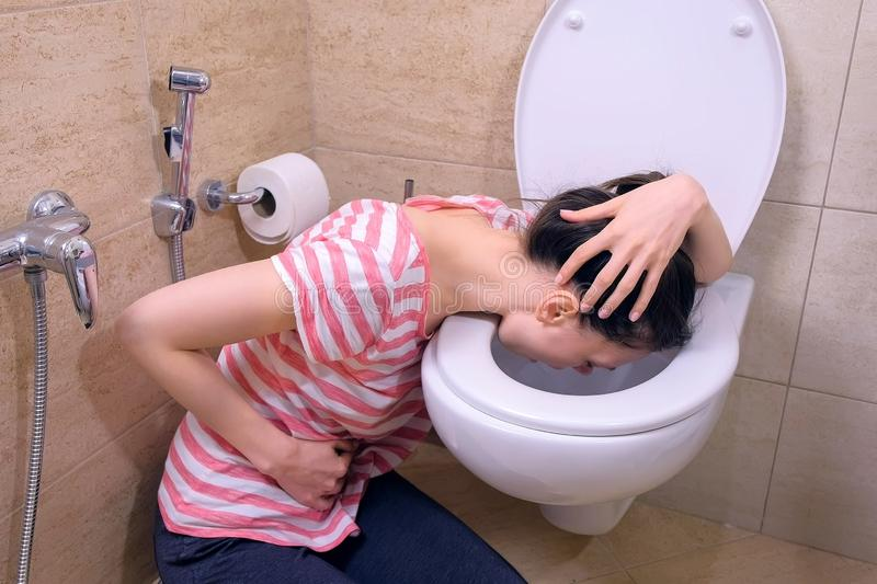 Young sick woman with pain in stomach is vomiting in toilet sitting on the floor at home, flu symptom. Young sick woman with pain in stomach is vomiting in stock photography