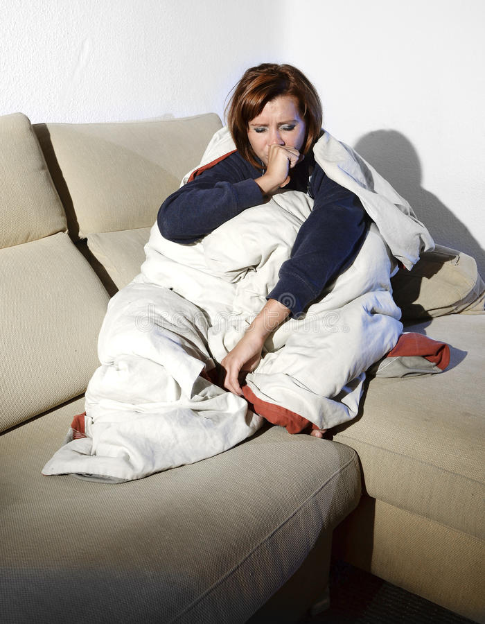 Young sick woman sitting on couch wrapped in duvet and blanket feeling miserable stock images