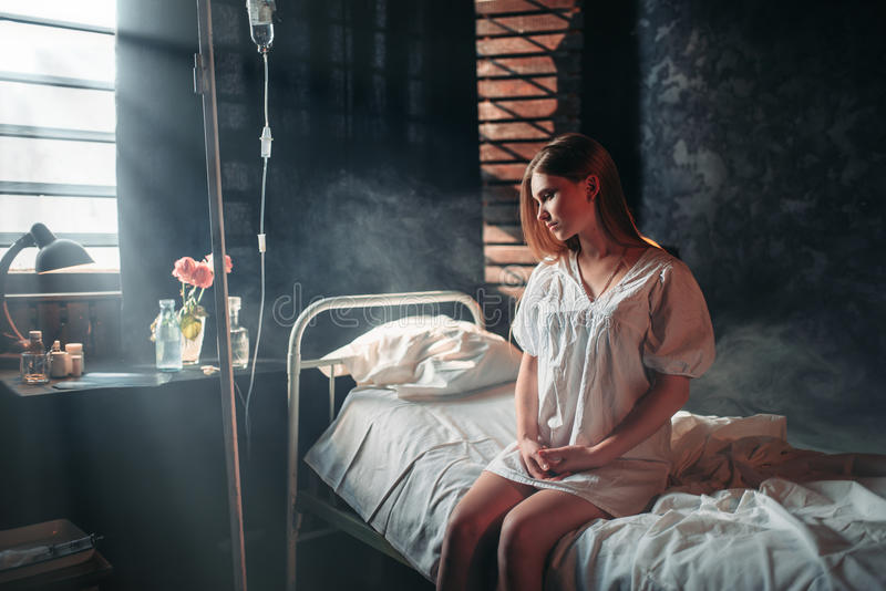 Young sick woman sitting on hospital bed on drip. Illness of female patient in clinic, health recovery and treatment stock photo