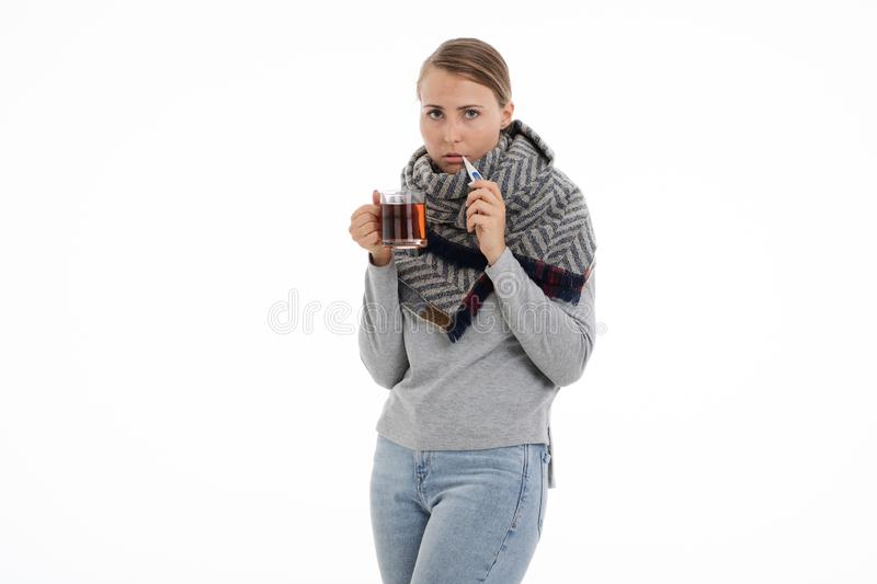 Young sick woman wrapped in a scarf. Cold, flu, illness. Young sick woman wrapped in a scarf on white background. Cold, flu, illness royalty free stock image