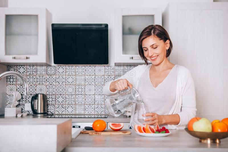 Young sincerely smiling female pouring a purified mineral water into transparent glass decanter at modern kitchen. Plenty of royalty free stock photo