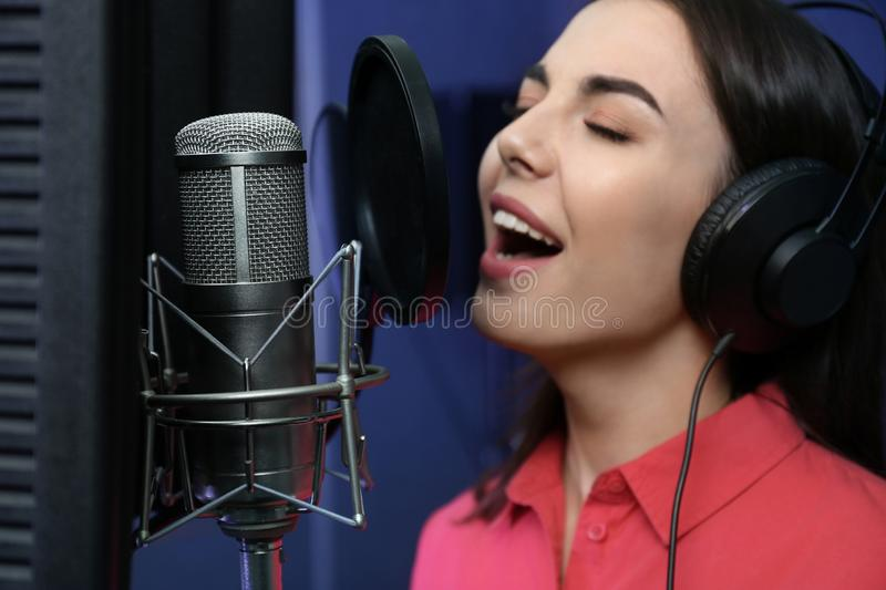 Young singer with microphone recording song. In studio royalty free stock images