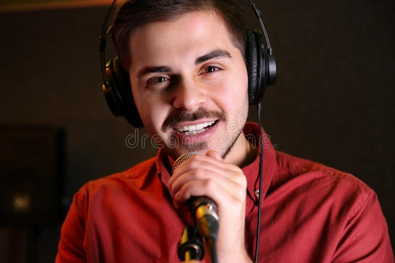 Young singer with microphone recording song. In studio stock image