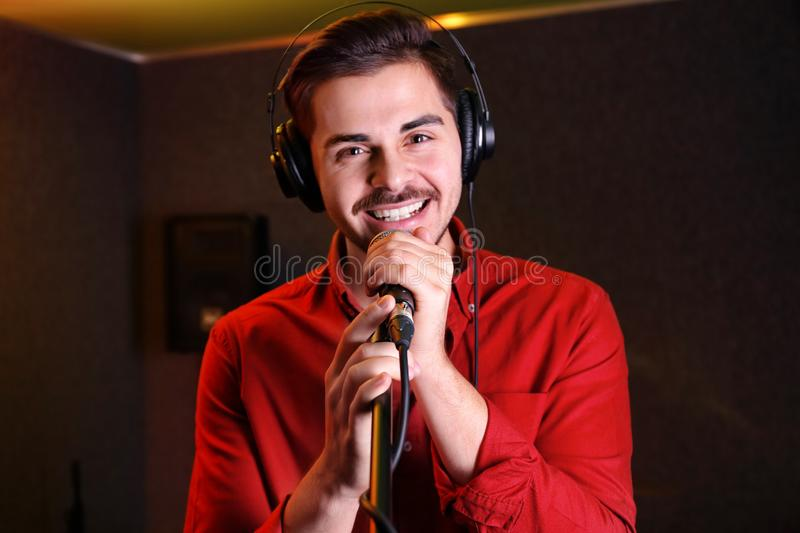 Young singer with microphone recording song. In studio stock photo