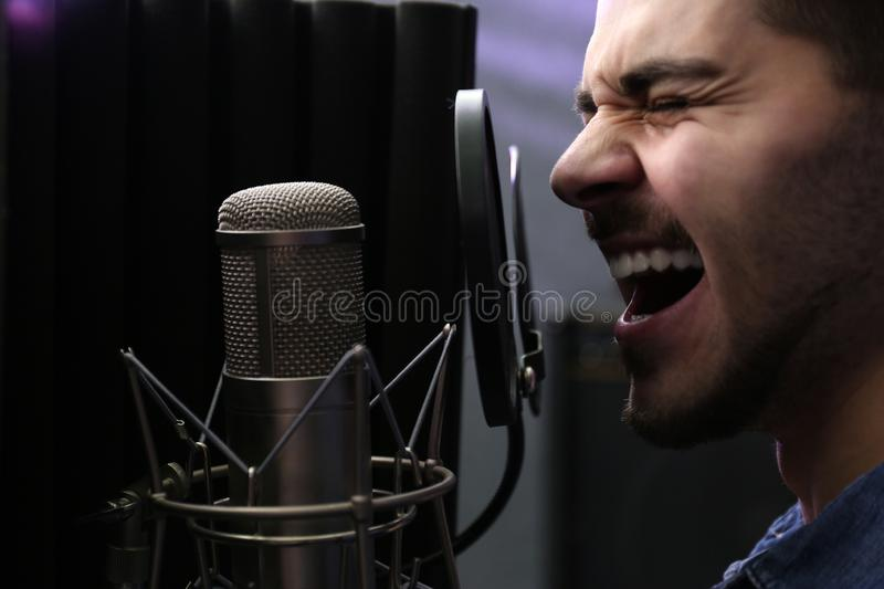 Young singer with microphone recording song. In studio royalty free stock image