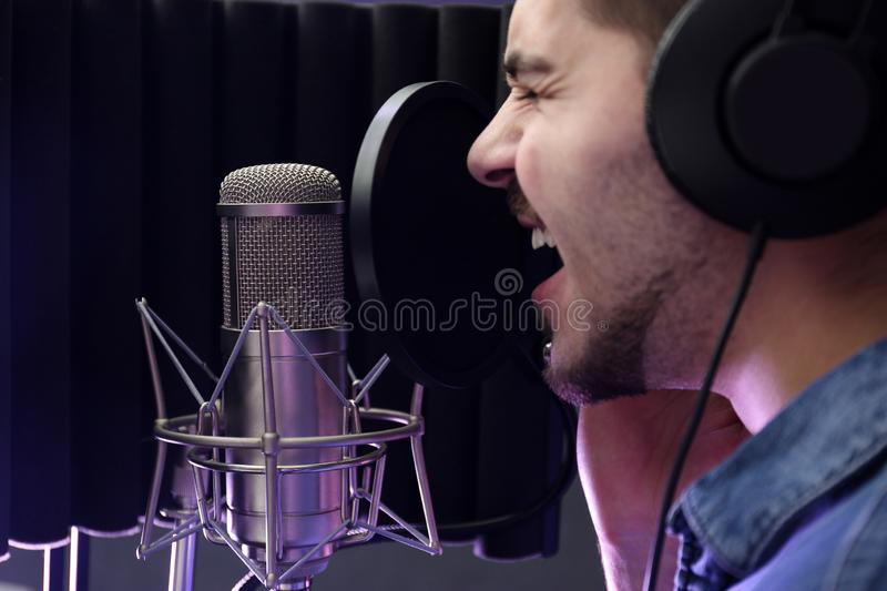 Young singer with microphone recording song. In studio royalty free stock photography