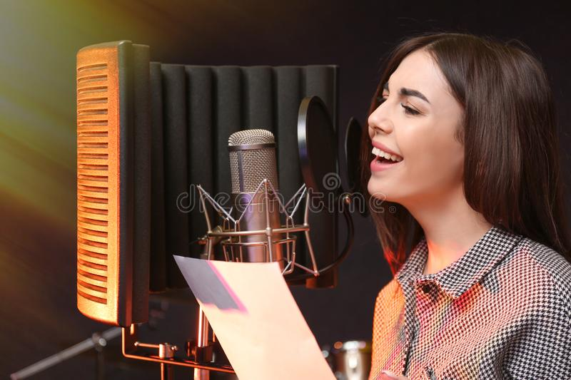 Singer with microphone recording song in studio. Young singer with microphone recording song in studio royalty free stock images