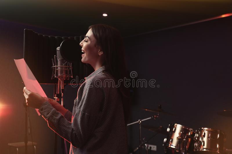 Young singer with microphone recording song in studio. Space for text stock images