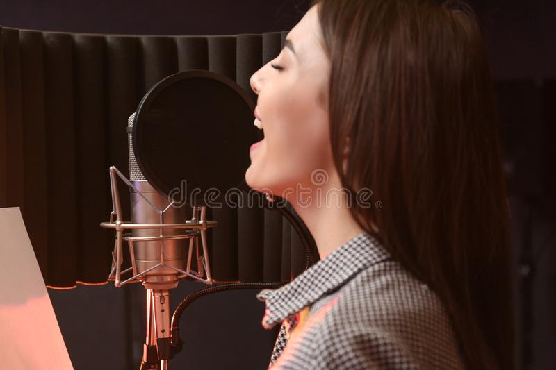 Young singer with microphone recording song. In studio stock photography