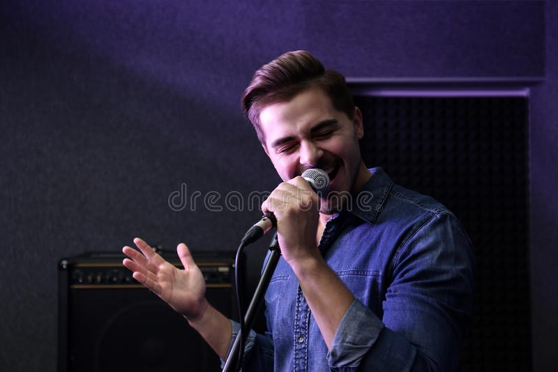 Young singer with microphone recording song. In studio stock photos