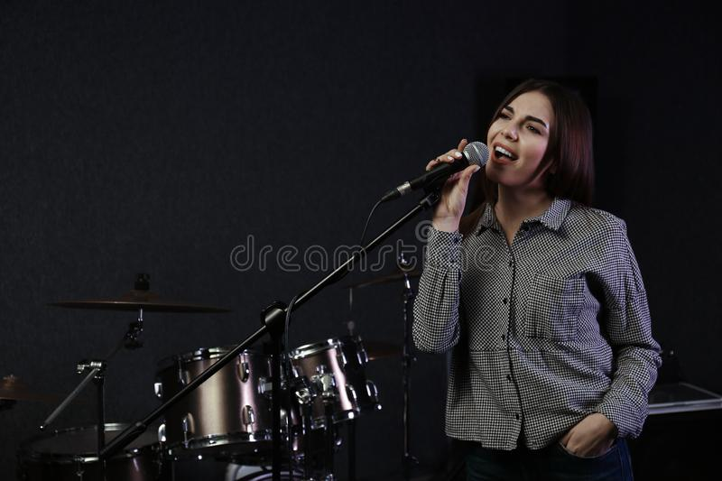 Young singer with microphone recording song in studio. Space for text royalty free stock photography