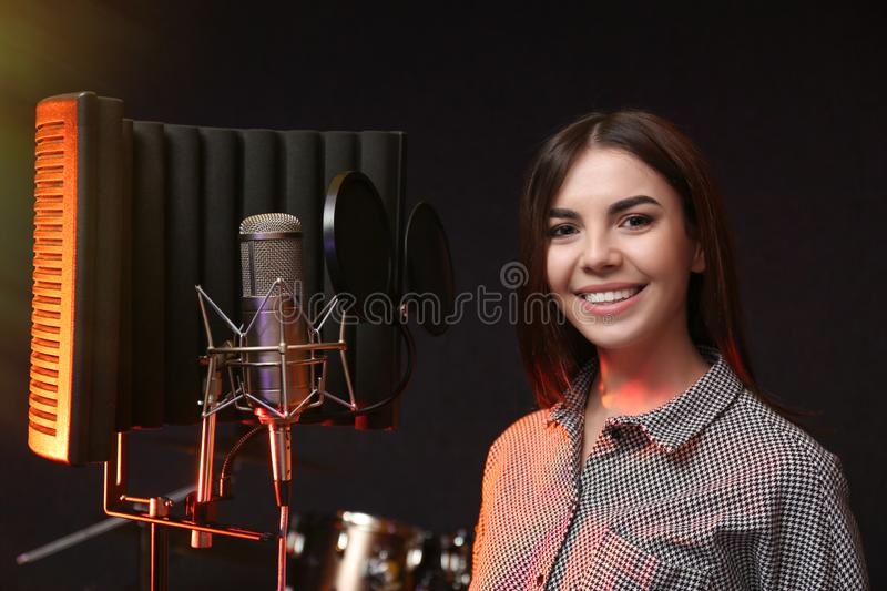 Young singer with microphone recording song. In studio stock images