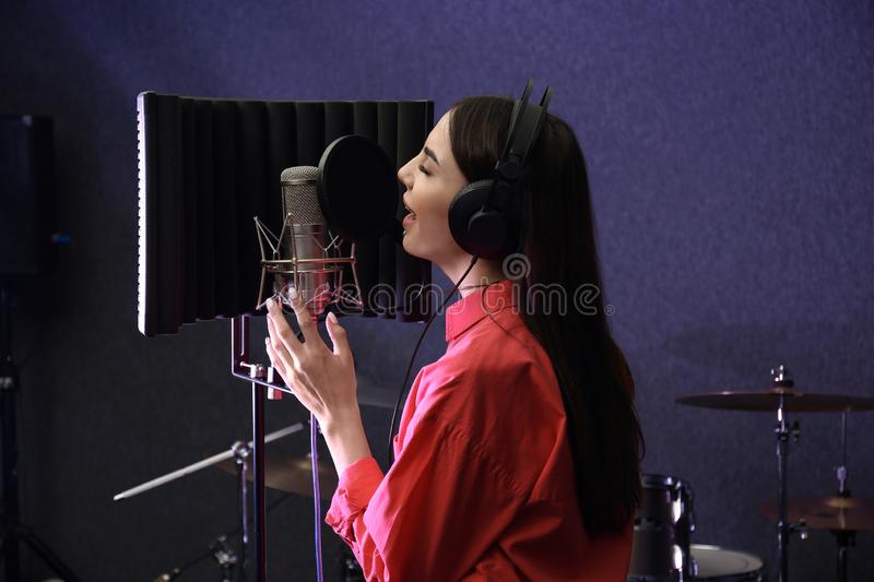 Young singer with microphone recording song. In studio royalty free stock photo
