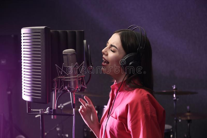 Young singer with microphone recording song. In studio royalty free stock photos