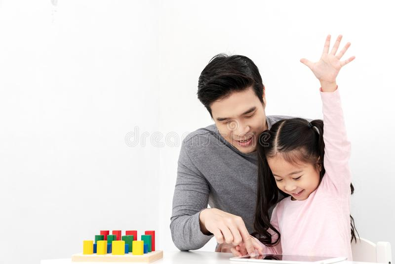 Young single dad play smart gadget and have fun with daughter sitting on kid desk table with colorful block toy beside copy space royalty free stock photos
